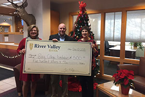 River Valley Bank employees holding a large check