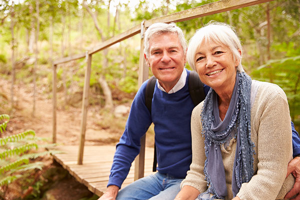Happy senior couple sitting on a bridge in forest