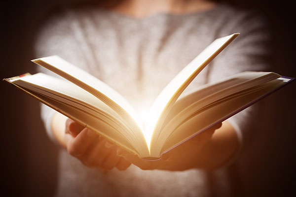 Light coming from book in gesture of giving, offering