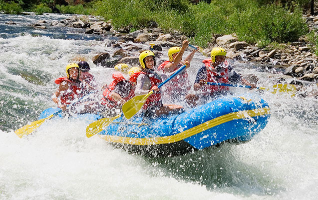 Group of young adults whitewater rafting