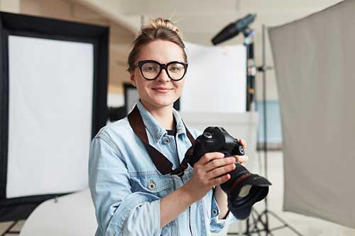 Female photographer holding camera in a studio.