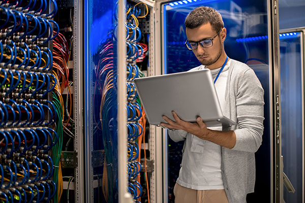 Network specialist with laptop in a server room