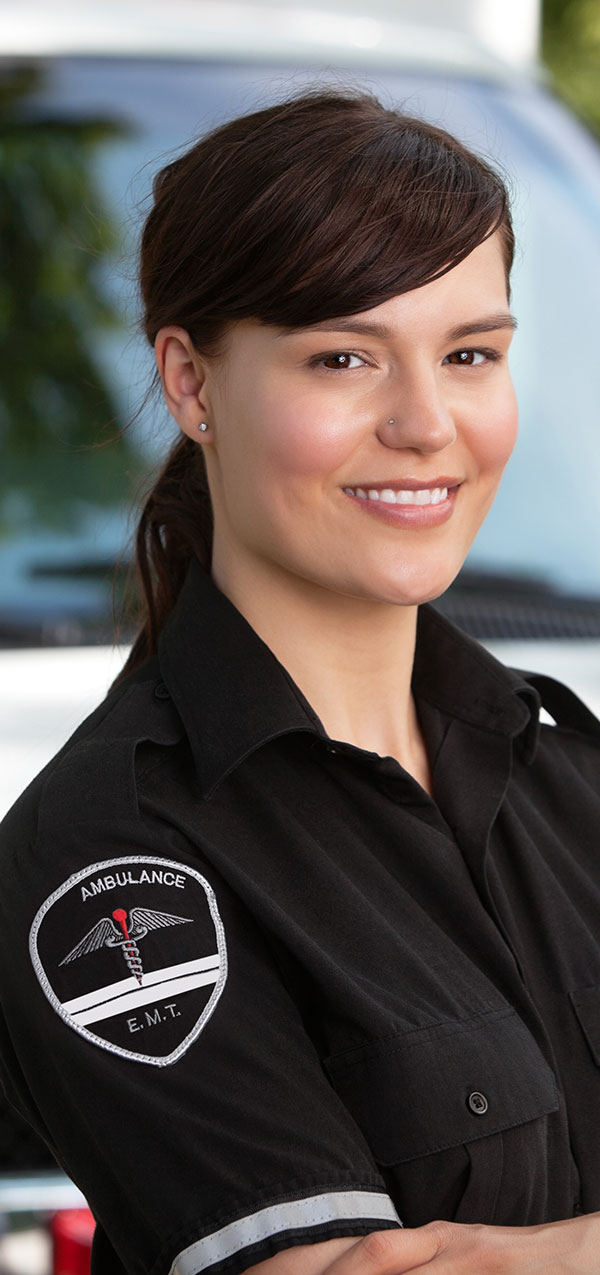 Female Emergency Medical Technician standing outside of her ambulance