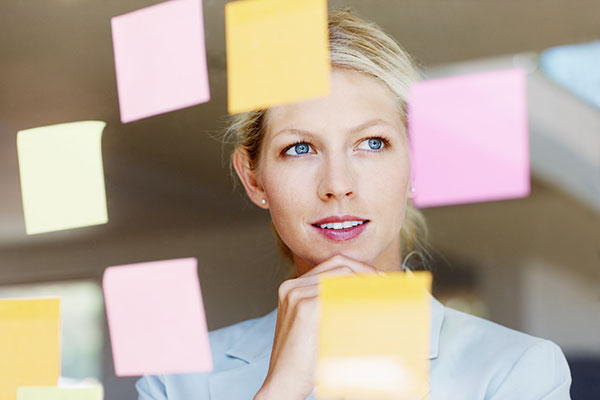 Business woman with sticky notes on glass window