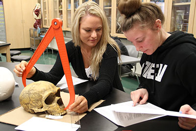 Two female students examing a skull in a lab
