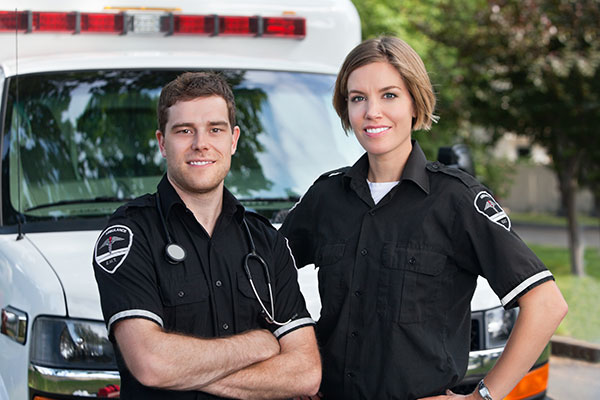 Paramedic team standing in front of ambulance