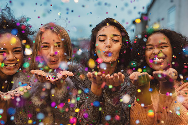 Young women blowing confetti from hands