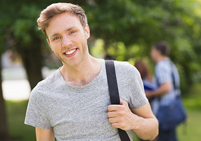 Male student smiling at camera outside on campus