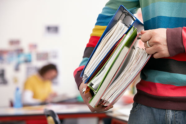 Close-up of a male college student holding books and binders