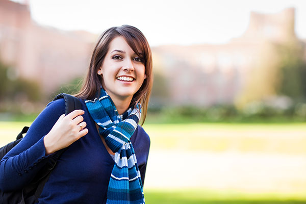 Smiling female college student holding a backpack