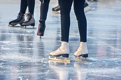 Closeup of people ice skating on a rink