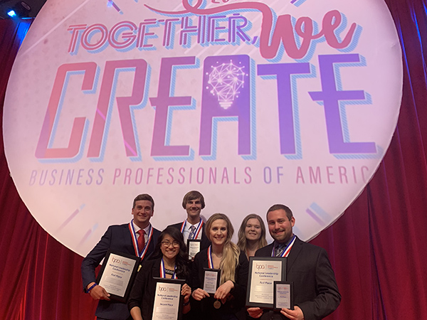 Six Bay College students, three men and three women, are pictured smiling with awards in front of a large pink banner that says Together We Create.