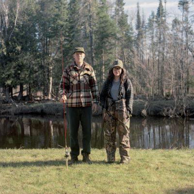 Man and woman are pictured outdoors in wooded setting wearing outdoor gear and carrying a fishing pole.