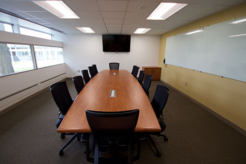 Board room with computer, confernce table, chairs and whiteboard