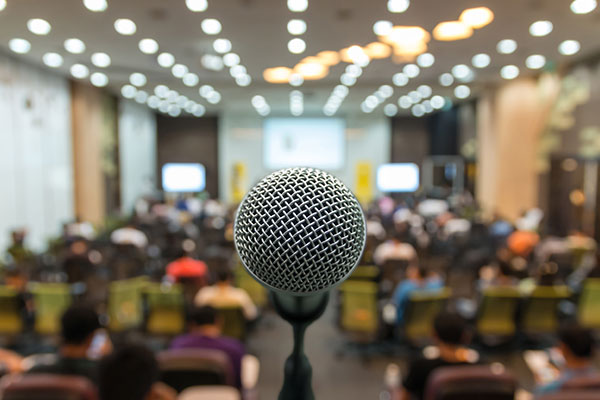 Microphone over a blurred photo of conference hall