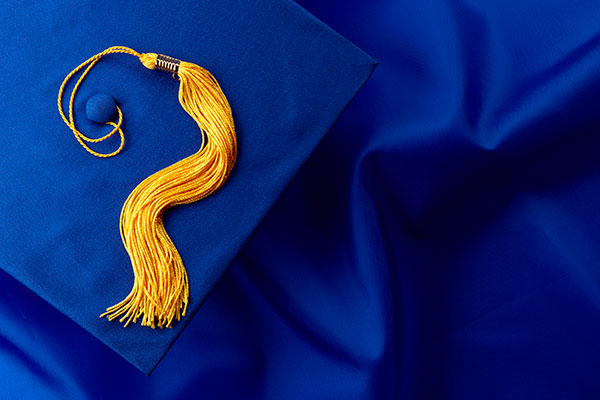 Blue mortarboard and yellow tassel shot on blue graduation gown