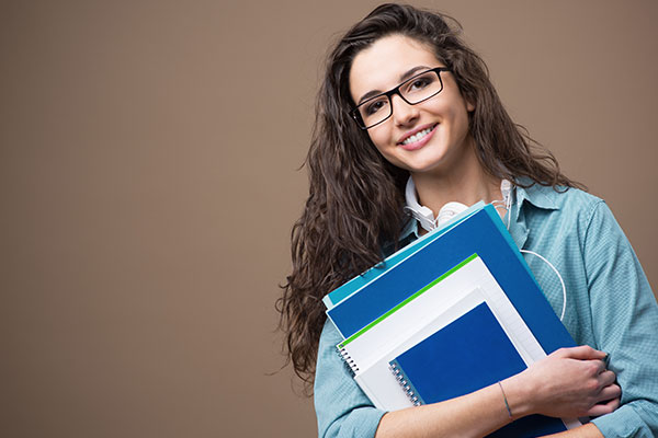 Smiling female college student holding books isolated on a brown background
