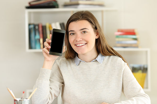 A happy female student showing a blank smart phone screen