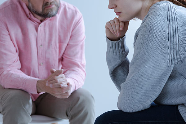 Close-up of a young sad woman sharing with counselor during counseling meeting