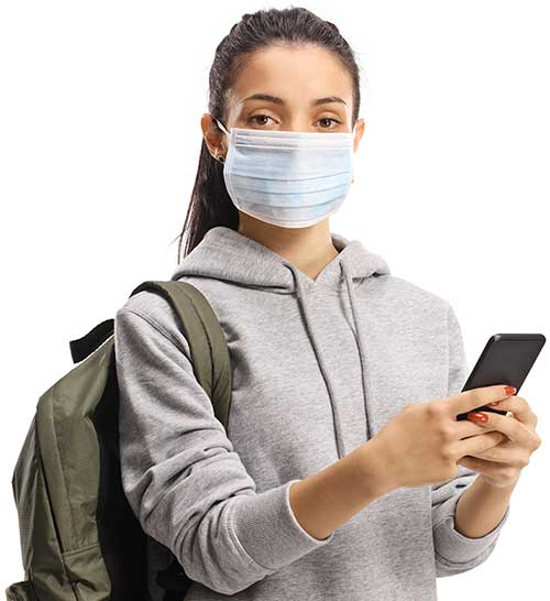 Female student wearing a protective mask while using a mobile phone
